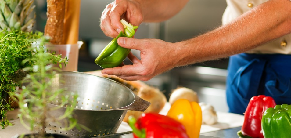 Man cooking in kitchen with peppers